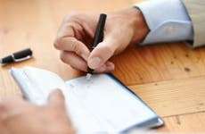 Professionaly dressed man writing a check © iStock
