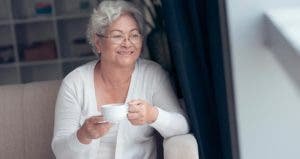 Woman enjoying a coffee by her window | iStock.com/DragonImages