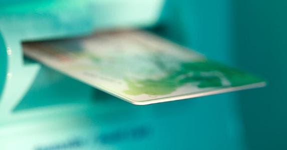 ATM card sticking out from machine slot | Derek E. Rothchild/Getty Images