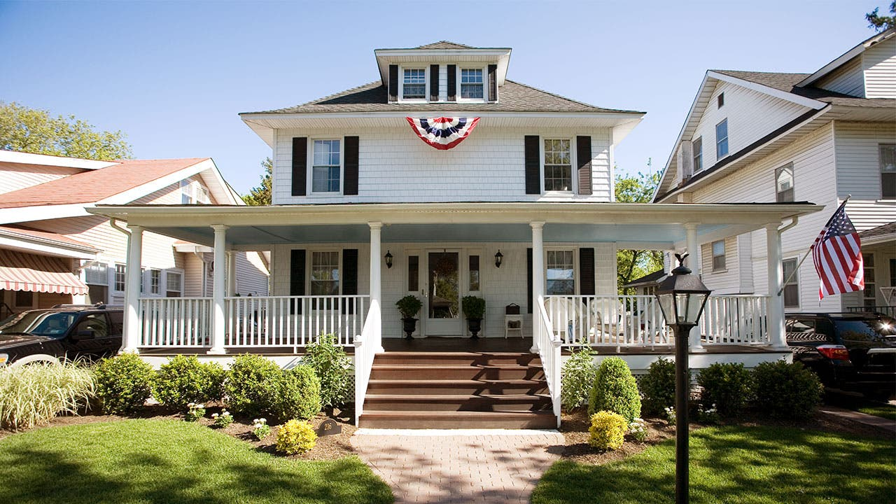 Colonial-style house with flags hanging | Nine OK/Getty Images