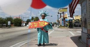Man in Liberty costume holding 'It's tax time' sign | Joe Raedle/Getty Images