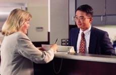 Bank teller with customer signing checkbook © Steve Smith/Shutterstock.com