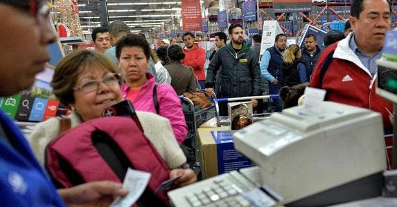 Shoppers waiting in checkout line on Black Friday | PEDRO PARDO/Getty Images
