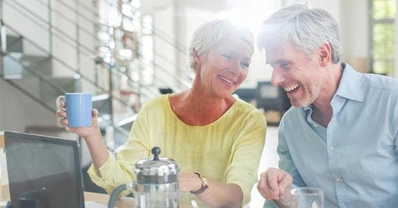 Senior couple laughing over coffee in kitchen table | Tom Merton/Getty Images
