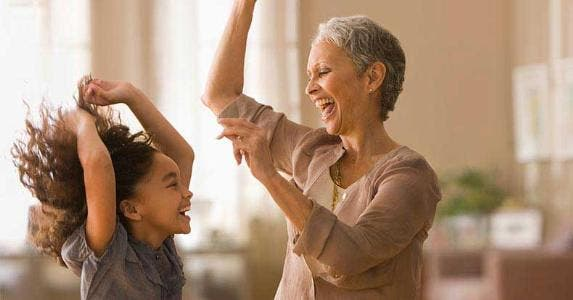 Grandmother and granddaughter dancing in living room | Blend Images/KidStock/Getty Images