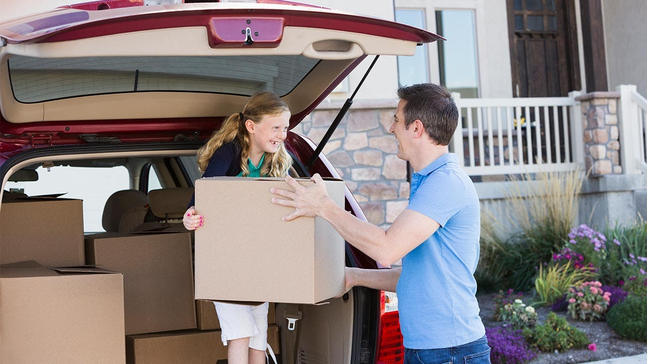 Father and daughter unpacking boxes from vehicle