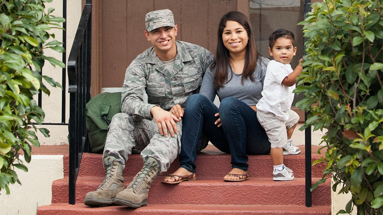 Service man with his wife and son on front porch