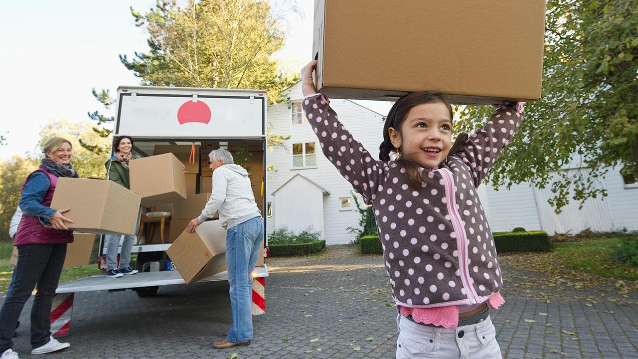 Family unpacking boxes from moving truck
