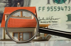 Small toy house with magnifying glass © Guy Shapira/Shutterstock.com