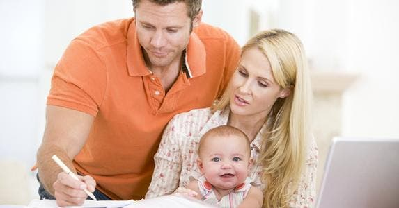 Couple with a baby on lap, working on paperwork © Monkey Business - Fotolia.com