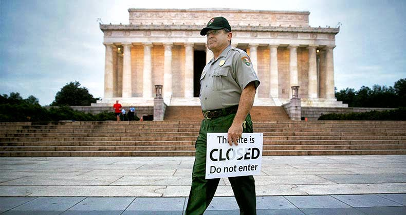 Government employee holding 'This site is CLOSED' sign |  Andrew Harrer/Bloomberg/Getty Images