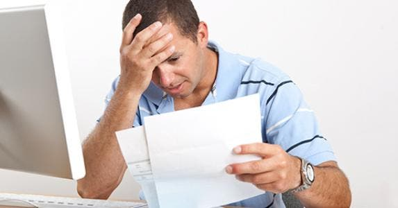 Man on facepalm overwhelmed with bills and paperwork © Barbara Reddoch - Fotolia.com