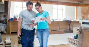 Couple standing in the middle of room being remodeled © iStock