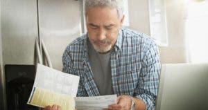 Older man looking down at bills | Jose Luis Pelaez Inc/Getty Images