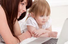 Mother with young daughter using computer