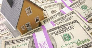 Toy house on top of stash of hundred dollar bills  © Kuzmafoto - Fotolia.com