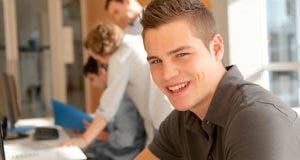 Smiling male student in classroom © Goodluz/Shutterstock.com