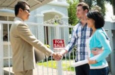 Real estate broker meeting clients outside house for sale © Dragon Images/Shutterstock.com