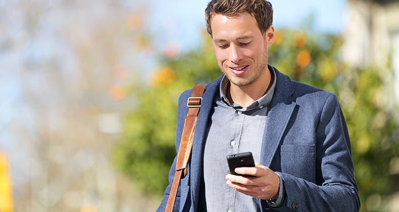 man with smartphone walking outside shoulderbag mst
