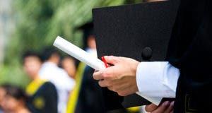Man holding graduation cap and diploma © xy - Fotolia.com