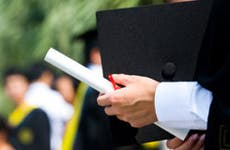 Man holding graduation cap and diploma © xy - Fotolia.com