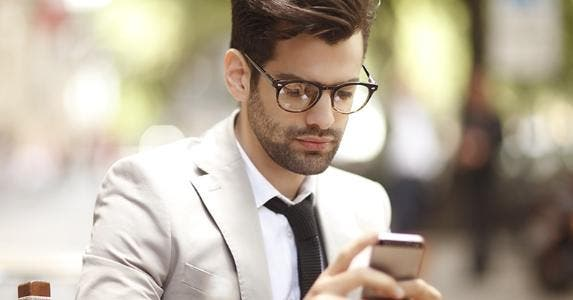 Young man with iPhone outside © Kinga/Shutterstock.com