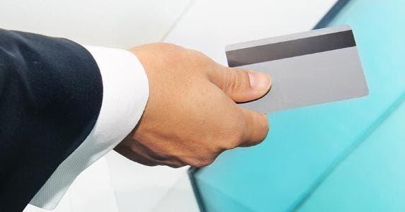 Business man holding silver card © Lucy Liu/Shutterstock.com