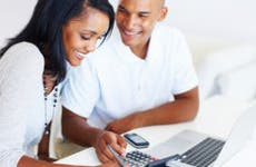 Happy young couple working on finances at home