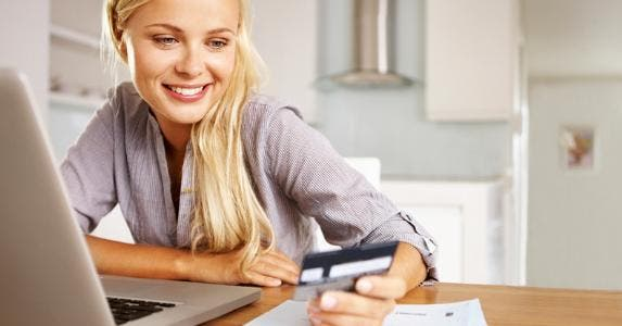 Woman smiling at her credit card © iStock