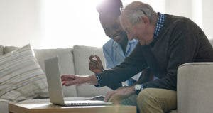 Man and caretaker opening laptop in living room © iStock