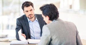 Boss and employee sitting at table, reviewing binder | iStock.com