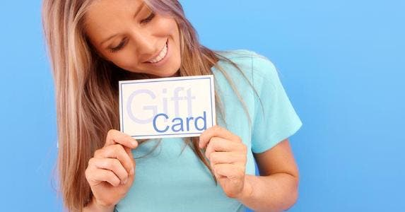 Young woman holding paper that says 'gift card' © iStock