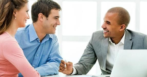 Young couple speaking with their financial adviser | iStock