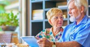 Upset senior couple holding tablet receives bad news | iStock.com/Juergen Sack