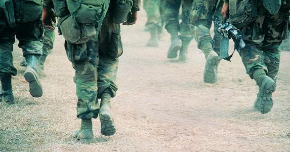 Military members in uniform walking through desert terrain | Frank Rossoto Stocktrek/DigitalVision/Getty Images
