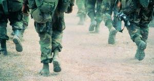 Military members in uniform walking through desert terrain | Frank Rossoto Stocktrek/DigitalVision/Getty Images