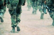 Military members in uniform walking through desert terrain   Frank Rossoto Stocktrek/DigitalVision/Getty Images