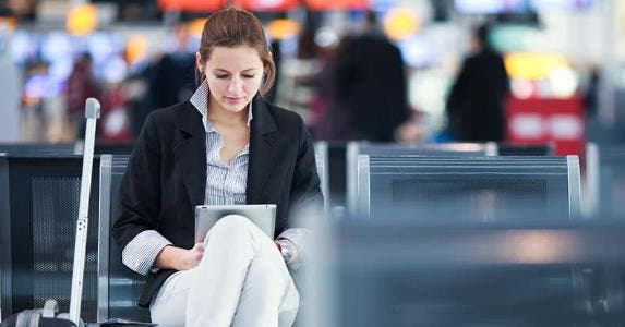 Young woman browsing tablet computer while waiting for her next flight © l i g h t p o e t/Shutterstock.com