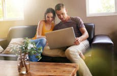 Young couple in living room couch browsing laptop © iStock