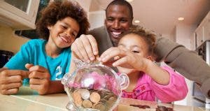 Family helping child save in piggy bank | Ronnie Kaufman/Larry Hirshowitz/Getty Images