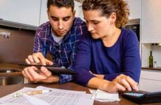 Young couple budgeting and using tablet computer in kitchen © iStock