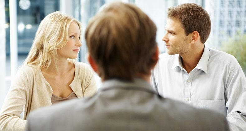Adviser meeting with a couple, at office desk | iStock.com