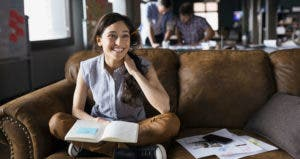 Employee smiling and sitting on couch   Hero Images/Getty Images