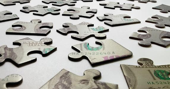 Puzzle pieces of $100 bill | Mike Kemp/Getty Images