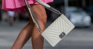 Woman walking with her white Chanel bag | Christian Vierig/Getty Images