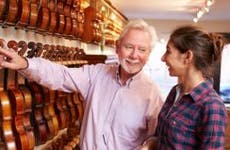 Violin seller showing violins to female buyer | Monkey Business Images/Shutterstock.com