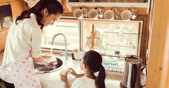 Mother and young daughter washing dishes