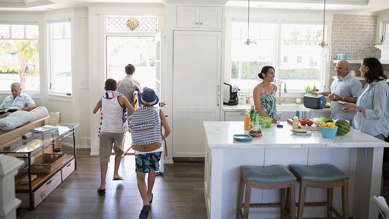 Family gathered together in kitchen, kids running out of the door
