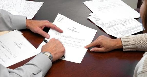 Adviser reviewing document with client | iStock.com/Jodi Jacobson