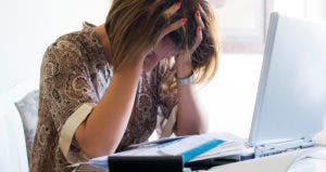 Stressed woman at her desk © iStock